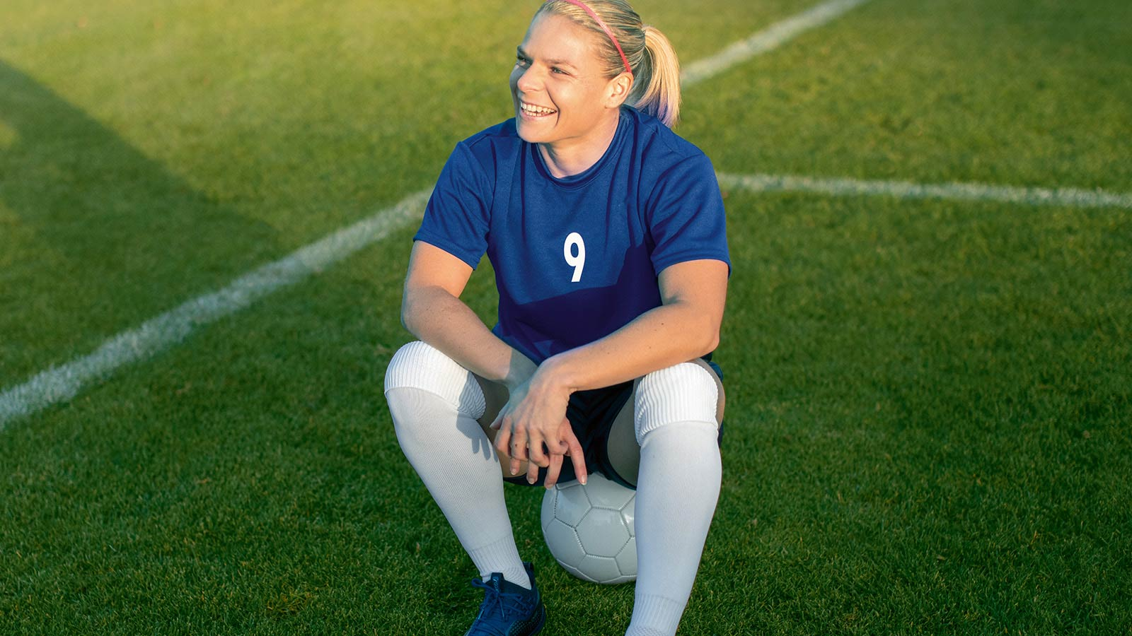 Eugenie Le Sommer sitting on top of a football and smiling.