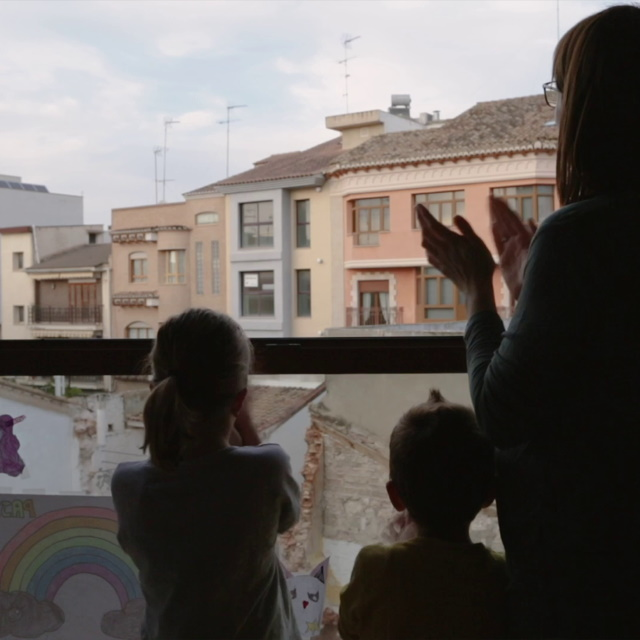 Family clapping at window